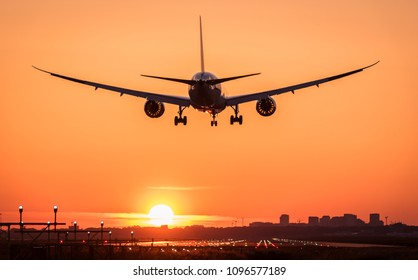 Beautiful aviation image taken during a perfect clear sunrise at the airport. The flying plane is almost landed.