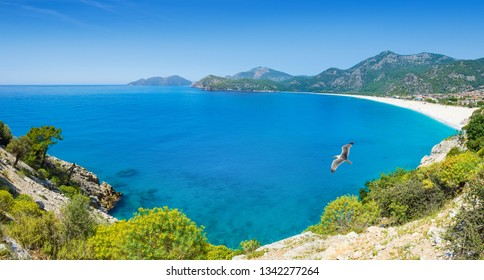 Beautiful azure lagoon and Blue Flag beach in Oludeniz, Fethiye district, Turquoise Coast of southwestern Turkey. Sunny summer weather with clear blue sky in Oludeniz.