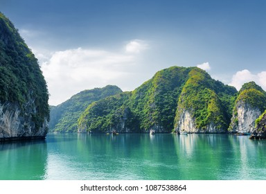 Beautiful azure water of lagoon in the Halong Bay (Descending Dragon) at the Gulf of Tonkin of the South China Sea, Vietnam. Scenic landscape formed by karst towers-isles on blue sky background.
