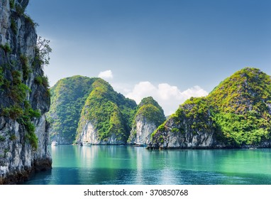 Beautiful azure water of lagoon in the Halong Bay (Descending Dragon Bay) at the Gulf of Tonkin of the South China Sea, Vietnam. Scenic landscape formed by karst towers-isles on blue sky background.
