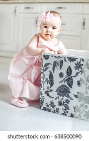 Beautiful babe gets toys from the box. Pink dress. The concept of childhood and education.