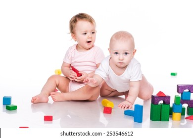 Beautiful babies building a castle with cubes isolated on white