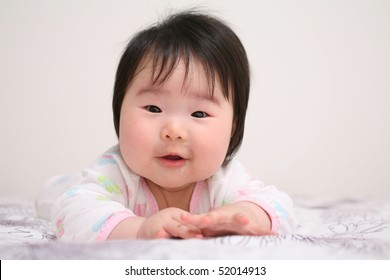 Beautiful Baby Asian Girl Infant Smiling While Crawling