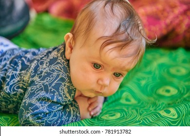 Beautiful baby with blue eyes lies on the belly in the bed
