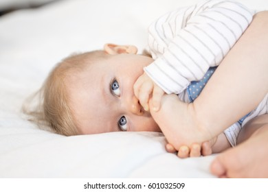 beautiful baby boy with blue eyes lying in bed on white background