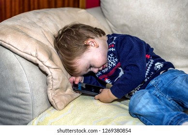 beautiful baby boy in a christmas jumper lying on the couch in the living room and playing with smartphone