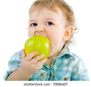 Beautiful baby boy eats green apple.