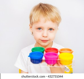 Beautiful baby boy holding new set of colored finger paints for children looking at camera. Bright colored cans and child isolated on white background. Red, blue, pink, orange, green, yellow colors