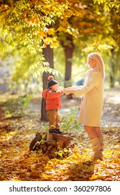 Beautiful baby boy and mother in autumn garden