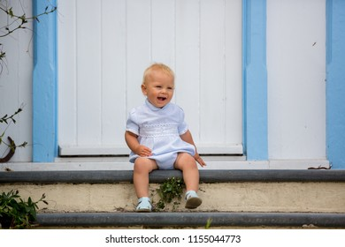 Beautiful baby boy, sitting on the front porch on the streets of Clovelly, nice old village in the heart of Devonshire, England