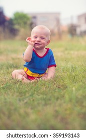 beautiful baby boy sitting on a grass with fingers in his mouth