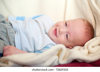 Beautiful baby boy smiling on blanket