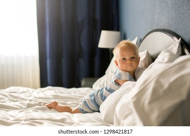 Beautiful baby boy, sweet child, lying in bed, playing in bed after bath, sleeping