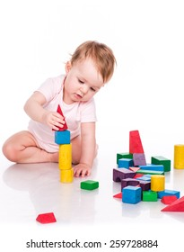 Beautiful baby building a castle with cubes isolated on white