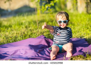 beautiful baby child in sunglasses gesture class outside