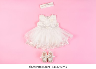 Beautiful baby dress with booties isolated on a pink background