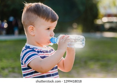beautiful baby drinks clean water from a bottle on a sunny day in nature