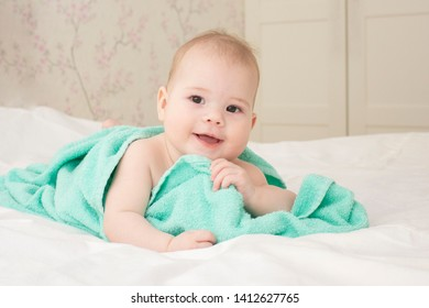 Beautiful baby girl 6 months playing with a towel after bathing. Laughing happy child portrait, good mood positive. Child face features soft focus