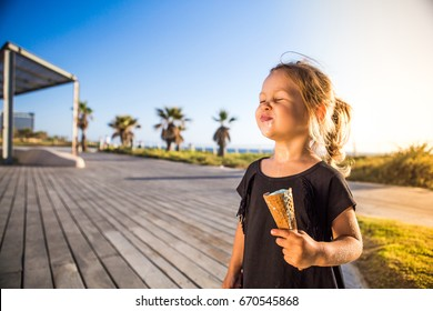 A beautiful baby girl in a black dress on a sunset with ice cream.