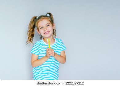 Beautiful baby girl brushing her teeth. Baby girl brushing her teeth and singing a favorite song.  Health care, dental hygiene, people and beauty concept. Mockup, free spase. Selective focus.