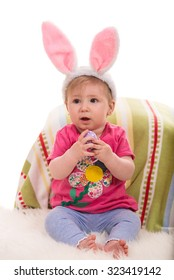 Beautiful baby girl with bunny ears holding Easter egg