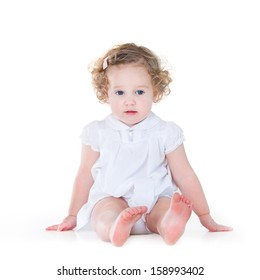 Beautiful baby girl with curly hair wearing a nice white dress on white background