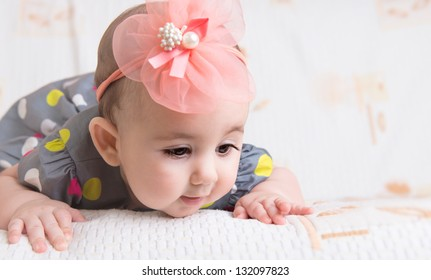 Beautiful baby girl with flower on head crawling