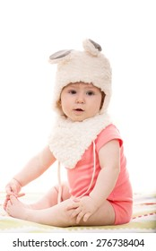 Beautiful baby girl in fluffy bunny hat  sitting on blanket