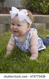 A beautiful baby girl laying on the grass, with a big smile showing off her teeth.