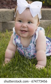 A beautiful baby girl, laying on the grass with a big smile, showing off her two teeth.
