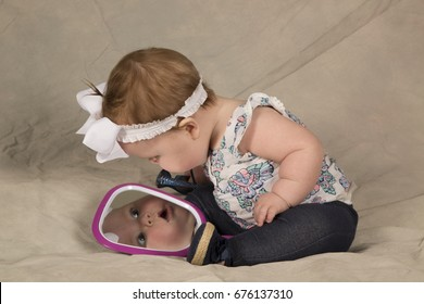 A beautiful baby girl looking at her face in the mirror.