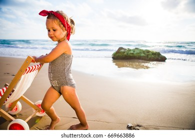 Beautiful baby girl on a beach on a sunset is playing.