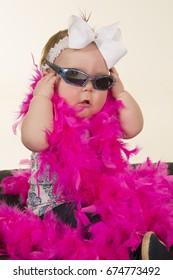 A beautiful baby girl, putting on her sunglasses, with her pink feathered boa. Showing off her style.