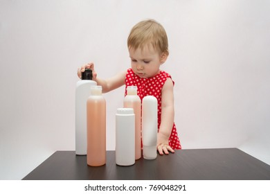 beautiful baby girl in red dress in peas stands near plastic bottles with shower gels or shampoo for body care on white isolated background
