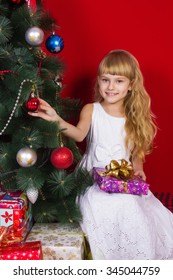 Beautiful baby girl sitting  near the Christmas tree in New Year's Eve smiling and holding a gift