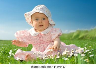 Beautiful baby girl wearing bonnet sat in field of flowers under blue sky.