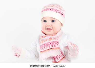 Beautiful baby girl wearing knitted hat, scarf and mittens