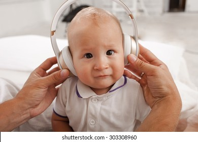 beautiful baby with headphones listening to music on white home background