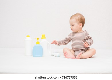 beautiful baby holding a bottle in the hand with shower gel, beside lies Baby cosmetic tubes on white isolated background