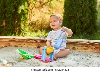 Beautiful baby playing in the sandbox