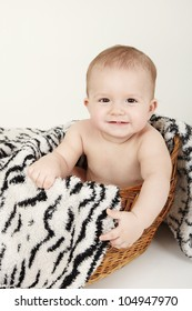 Beautiful baby portrait with cute facial expression sitting in a basket