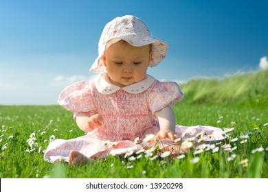 Beautiful baby sat in field looking at flowers.
