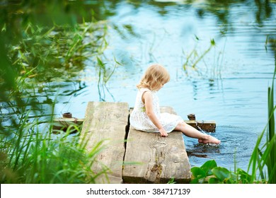 Beautiful baby sitting on the beach in a white dress. Girl looking at the water. The child  on the bridge by the river. Lots of lush greenery.