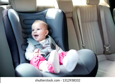 Beautiful baby smiling and having fun while being in the infant car seat