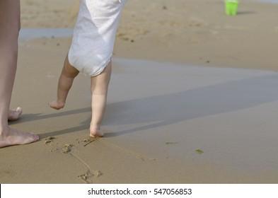Beautiful baby walking on the sand in Bulgarian resort