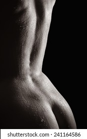 Beautiful back of a nude woman with wet body, monochrome closeup in front of black background