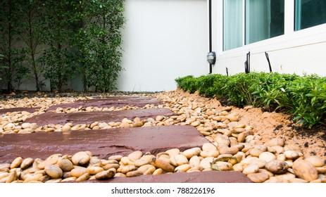 beautiful back yard of the house in Bangkok, decorated with river stone, sandstone walkway and many kinds of bushes