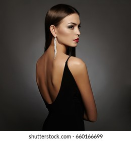 beautiful back of young woman in sexy dress.luxury beauty girl in a black sexy dress with open back wearing jewelry