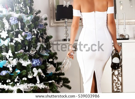 beautiful back of young woman in a white sexy dress with champagne elegant fashion glamour