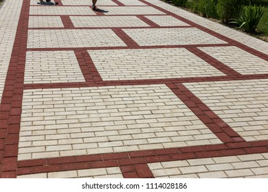 beautiful background laid paving slabs on pedestrian path. Monotonous pattern of multicolored glazed paving slabs. Photo site with paving slabs with small defects and cracks coming out in perspective